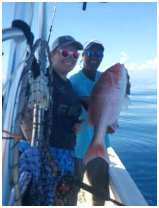 Captain Corey of On The Hook Charters with a Red Snapper