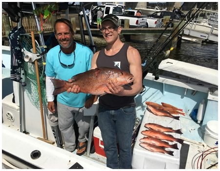 Captain Corey with guest angler holding a nice mangrove snapper