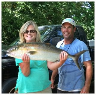 A happy customer shows off her amberjack next to Captain Corey of On The Hook Charters in Daytona Beach, Florida